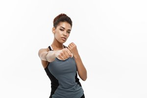 Healthy and Fitness concept - portrait of African American woman punching in air with confident face. Isolated on white background.