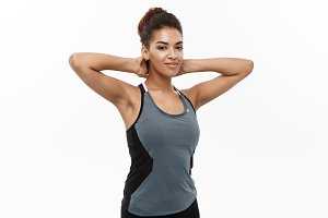 Healthy and Fitness concept - portrait of African American girl posing with fitness clothes over white studio background.