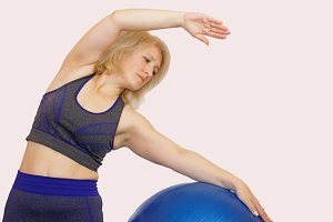The woman performs a physical exercise to reduce weight