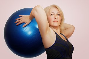 A middle-aged woman performs an exercise from Pilates