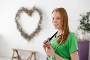 Beautiful female doctor cardiologist or neurologist and heart shape on background. Healthcare, healthy heart concept