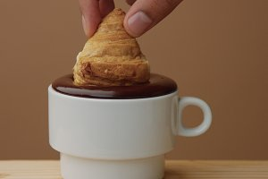 closeup of croissant immerse into hot chocolate in cup