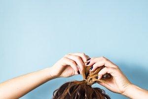 Simple hairstyle bun on a blue backg