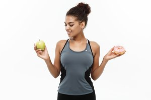Healthy and diet concept - Beautiful sporty African American make a decision between donut and green apple. Isolated on white background.