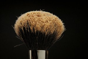 closeup of black brush with a facial powder on it