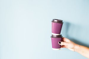 Violet cups of coffee in hand