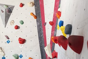 Grey wall with climbing holds.