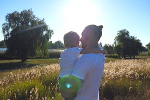 Young dad holding his son on hands at the meadow and talking something to him. Happy family spending time together on a sunny day. Beautiful landscape at background. Close up Rear back view