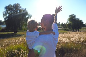 Father and little child waving their hands at the meadow. Young dad holding his son on arms at nature. Happy family spending time together. Summer landscape at background. Close up Rear back view
