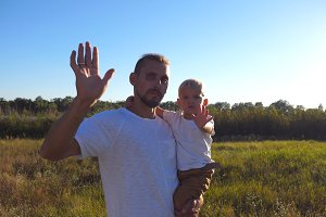 Portrait of happy family waving their arms into camera at the meadow. Young dad holding his son on hands at nature. Father and child spending time together. Nature landscape at background. Close up