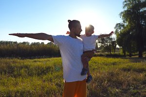 Portrait of handsome father and little son playing raised hands as airplane at the meadow. Young dad holding his son on hands at the field. Family spending time together at nature. Close up