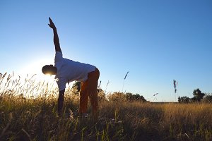 Sporty man practicing yoga on mat at the meadow. Young guy training at the field on a sunny day. Summer landscape at background. Concept of healthy active lifestyle. Low angle view