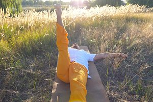 Top view of young man lying on mat at the meadow and practicing yoga on a sunny day. Sporty guy doing stretch exercise at the field. Summer landscape at background. Healthy active lifestyle Close up