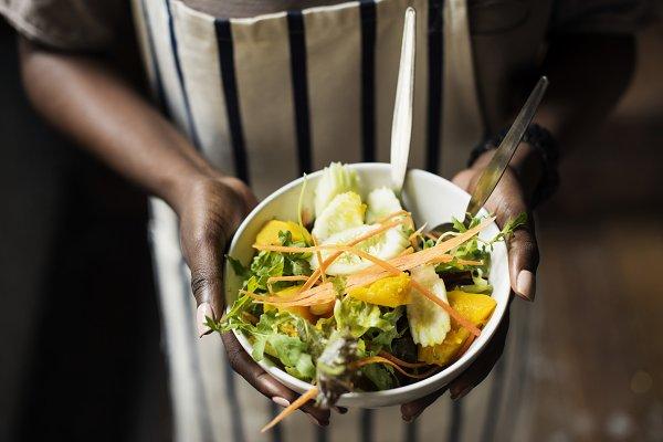 Black woman holding the salad bowl