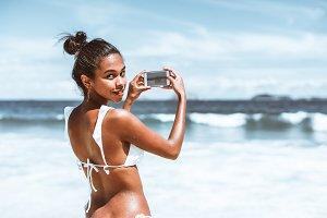 Black girl taking photo on beach