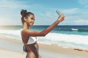 Girl is taking selfie on the beach