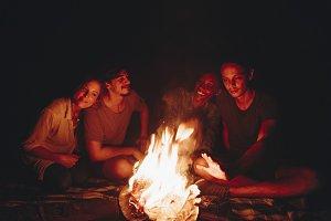 Friends sitting around a bonfire