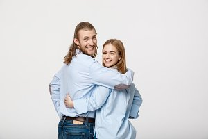 Portrait of cheerful young couple standing and hugging each other on isolated white background