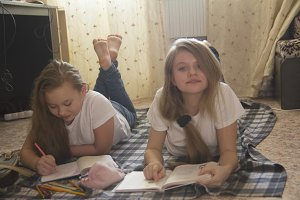 Two girl teens who spend time at home reading a book and drawing while lying on the floor