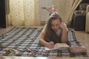 Girl teen who spend time at home drawing while lying on the floor