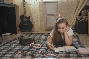 Girl teen who spend time at home drawing sketches in a notebook while lying on the floor