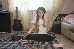 Teen girl listening to music in headphones sitting on the floor at home