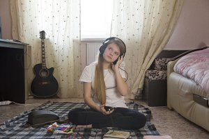 Teen girl listening to music in headphones using smartphone and drawing sitting on the floor at home