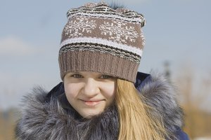 Portrait of teen girl in cap and jacket with fur collar in winter outside