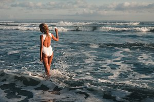 Attractive young blonde woman walking at beach