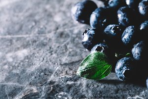 Fresh juicy blueberries and a green