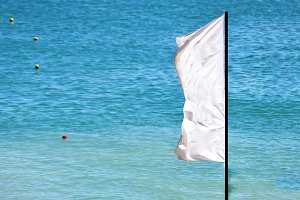 a waving white flag with blue sea