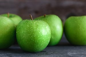 Wet fresh green apples in a row