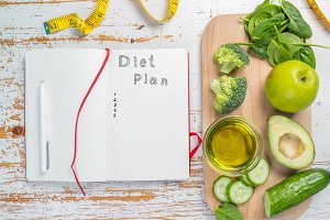Diet plan concept - selection of green food and note pad