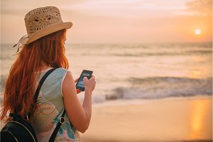 young woman uses a smartphone on the beach at sunset