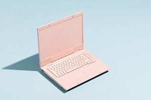 Retro pink laptop on a pastel blue b