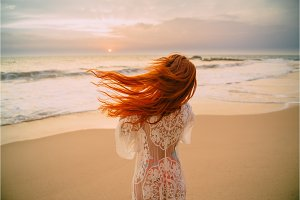 young red-haired woman with flying hair on the ocean, rear view