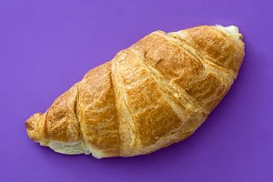Croissant on violet background