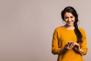 Studio portrait of a young woman with smartphone.