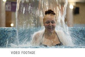 Middle-aged woman under water stream