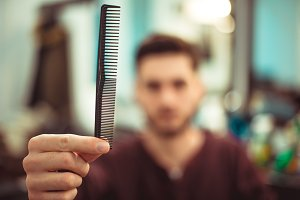 A man holding a comb .
