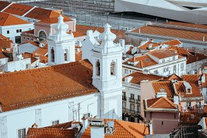 Rooftops, church of Alfama district in Lisbon. Cruise boat on the Tagus River. Lisbon Lisboa Lissabon