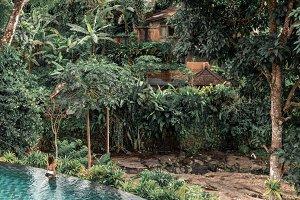 Happy young woman in a tropical infinity pool. Luxury resort on Bali island.