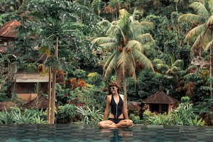 Happy young woman in a tropical infinity pool. Luxury resort on Bali island.