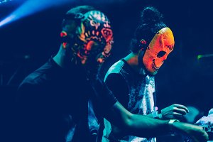 Djs with mask playing music at party