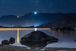 Night sky stars over mountain lake