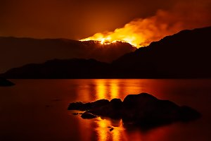 Forest fire reflecting in lake