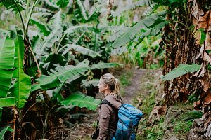 Blond yong women with camera and blue backpack walking through banana plantation on the trekking route to paul valley. Santo antao island. Cape verde