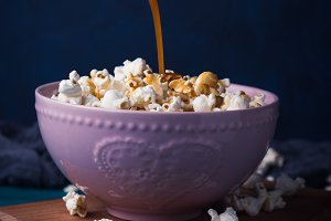 Pouring caramel on popcorn in bowl