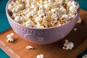 Popcorn in pink bowl on dark background