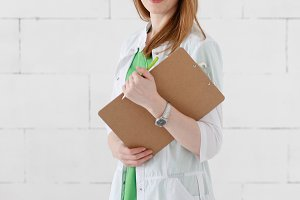 Portrait of a smiling young female doctor with medical gown and clipboard. Good healthcare concept